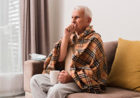 Homem idoso, envolvido por uma manta, com o punho direito cobrindo a boca, indicando doença respiratória.