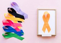 yellow-ribbon-on-white-wooden-frame-near-the-row-of-colorful-awareness-ribbon (2)
