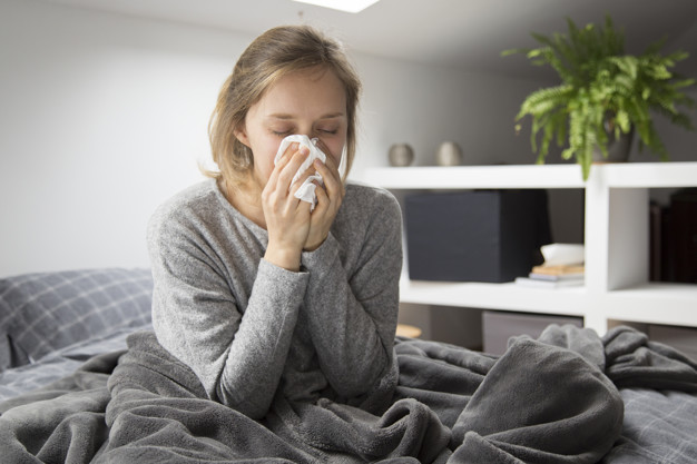Sick young Caucasian woman covered with grey blanket sitting on bed with closed eyes, blowing nose with napkin. Illness, pain concept