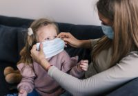 menina-bonitinha-e-mae-usando-mascara-facial-sentada-na-cama-em-casa-consolando-a-triste-filha-pre-escolar_231208-146